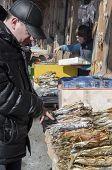 Irkutsk region, Russia-March,23 2014:Man chooses cisco in the fish market in Listvyanka, Lake Baikal