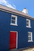 Blue Painted House With A Red Door