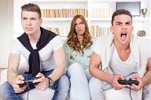 Bored Women Between Two Casual Passionate Men Playing Video Game