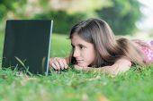 Teenage girl laying in the grass and using her laptop computer