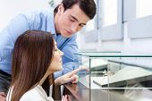 stock photo of jewel-case  - Girl with male selects expensive jewelry at jeweler - JPG