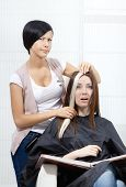 Hair stylist tries lock of dyed blond hair on the client sitting on the chair in the hairdresser's