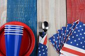 High angle photo of a Fourth of July picnic table setting. The red white and blue items are on a woo