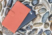 foto of floor covering  - Smartphone leather case cover on gravel texture floor - JPG