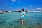 Kid girl walking at formentera in Estany des Peix lake rear view