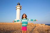 Happy open arms kid girl in Mediterranean lighthouse at formentera