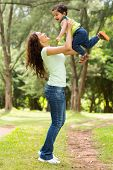 stock photo of indian  - beautiful young indian woman playing with baby boy outdoors - JPG
