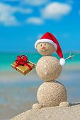 Sandy Snowman At Beach In Christmas Hat With Golden Gift.