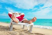 Sunbathing Santa Claus Relaxing In Bedstone On Beach - Christmas Concept
