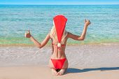 Beautiful Blonde Woman In Red Christmas Hat On Sea Beach.