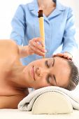 stock photo of ear candle  - Woman relaxes in the study of natural medicine - JPG
