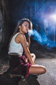 asian woman sitting on skate and smoking