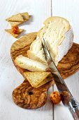 French soft spicy cheese from cow's milk on chopping board olive wood