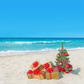 Christmas Tree And Golden Gift Boxes With Big Red Bow On The Sea Beach