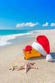 Santa Claus Hat And Christmas Gift Box On The Seashore With Sea Stars Against Blue Sky