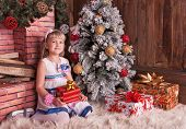 Happy Small Girl With Christmas Gift Box In Comfortable Interior
