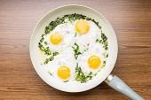 Fried Eggs In Frying Pan On Wood Background