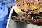 pic of rain  - Man Cleaning a rain gutter in Close up - JPG