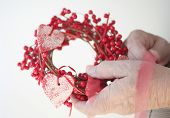Man ties ribbon on berry and heart Christmas wreath