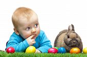 stock photo of easter bunnies  - Cute young child is lying in meadow together with Easter bunny and colorful Easter eggs in meadow - JPG