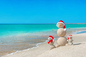 foto of hot water  - Snowmans family at sea beach in santa hats - JPG