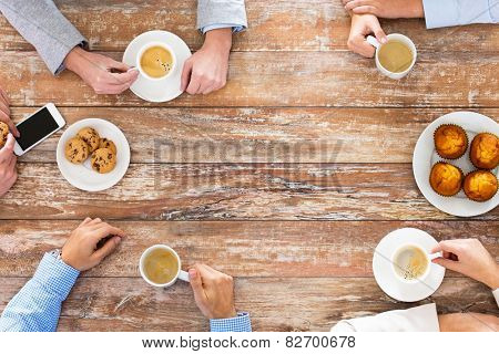 business, people and team work concept - close up of creative team meeting and drinking coffee durin