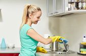 people, housework and housekeeping concept - happy woman in protective gloves cleaning tap with rag at home kitchen