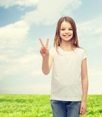 gesture and happy people concept - smiling little girl in white blank t-shirt showing peace gesture with fingers