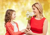 people, holidays, relations and family concept - happy little daughter giving flowers to her mother over yellow lights background