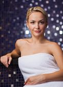 people, beauty, spa, healthy lifestyle and relaxation concept - beautiful young woman sitting in bath towel