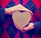hands holding a valentine's day heart on a solid background toned with a retro vintage instagram filter effect