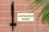 Pair of chopsticks and Japanese Food text on brown bamboo mat background