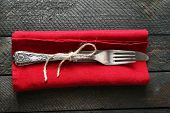 Silverware tied with rope on red napkin on wooden planks background