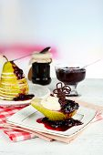 Tasty dessert with pear, cream and berry sauce on plate, on color wooden table, on bright background