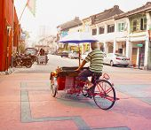 Malaysia, Penang, Georgetown - Circa Jul 2014: A Pedicab Driver Pedals His Cycle Rickshaw, Laden Wit
