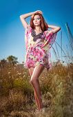 Beautiful young woman in wild flowers field on blue sky background. Portrait of attractive redhair