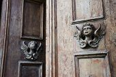foto of neo-classic  - Sculpture of an angel on a wooden door in Italy - JPG