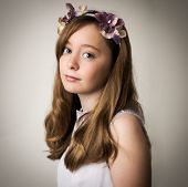 foto of tiara  - Studio portrait of a beautiful teenage ginger girl wearing a flower tiara and a pink outfit isolated against a grey background - JPG