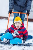 picture of snow shovel  - Funny little child having fun with riding on snow shovel during his father cleaning road from snow outdoors on cold day - JPG