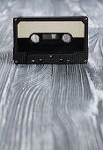 Music Concept. Black Audio Cassette On The Gray Wooden Background. Vintage, Retro Style. Soft Focus.