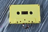 Yellow Audio Cassette On The Gray Wooden Background. Vintage, Retro Style. Soft Focus.