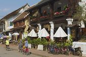 People ride bicycles by the street in Luang Prabang, Laos.
