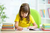 Cute kid girl reading story from book in nursery