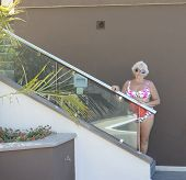 Woman Is Standing Near Stairway Of Hotel Swimming Pool.