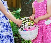 Two Girls Hands Holding An Easter Basket