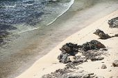 stock photo of footprints sand  - narrow beach with sand and limestone with footprints and shallow water - JPG