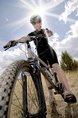 Woman Riding Mountain Bike with Sun and Sky in background