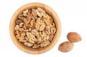 Cracked walnuts in wooden bowl with two nuts near isolated