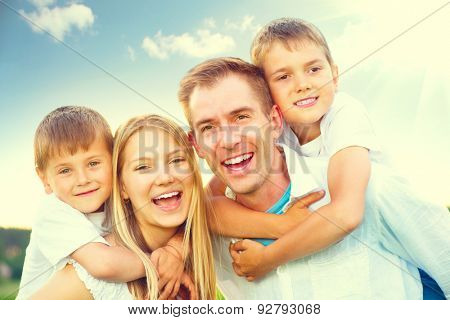 Happy joyful young family father, mother and kids having fun outdoors, playing together outside. Mom