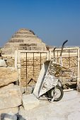 picture of wheelbarrow  - The Step Pyramid Of Djoser and wheelbarrow used for some works on site in Saqqara Egypt - JPG